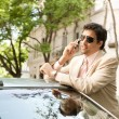 Stock Photo: Young businessmhaving conversation on his cell phone while leaning on his car