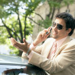 Young attractive businessman leaning on the top of a car — Stok fotoğraf
