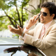 Stock Photo: Young businessmhaving conversation on his cell phone