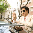 Stock Photo: Young businessmusing his cell phone while leaning on his car