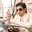 Young attractive businessman using his cell phone — Stok fotoğraf