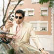 Young attractive businessman leaning on the top of a car — Stock fotografie