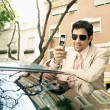 Stock Photo: Young attractive businessmleaning on top of car in classic street