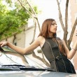 Stock Photo: Young attractive businesswoman using a smart phone while leaning on a shiny car