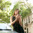 Young attractive businesswoman using a smart phone while leaning on a shiny car — Stock Photo