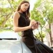 Young attractive businesswoman using her smart phone while leaning on a car — Stock Photo