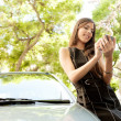 Young attractive businesswoman using her smart phone while leaning on a car — Stock Photo #21926583