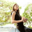 Stock Photo: Young attractive businesswomusing her smart phone while leaning on car