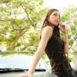 Side view of an attractive businesswoman leaning on a car — Stock Photo