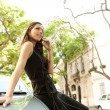Attractive businesswoman leaning on a car in a tree lined street — ストック写真