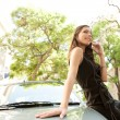 Profile view of an attractive businesswoman leaning on a car — Stock Photo