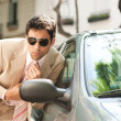 Close up view of an attractive businessman grooming himself using a car mirror outdoors — Stock Photo