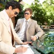 Two businessmen working while leaning on a luxury car in a tree lined street in the city. — Stock Photo