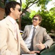 Two businessmen having a conversation while leaning on a car in a tree lined street in the city — Stockfoto