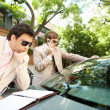 Attractive businessmen working together outdoors while leaning on a luxury car  — Stock Photo
