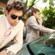 Attractive businessmen working together outdoors while leaning on a luxury car — Zdjęcie stockowe