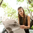 Stock Photo: Beautiful young businesswoman reading a newspaper while leaning on a car