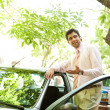 Young successful businessman with his car having a phone conversation using a hands free set — Stock Photo