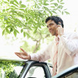 Stock Photo: Attractive businessmleaning on car's top while making phone call