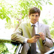 Attractive young businessman using a digital tablet while leaning on the door of his car — Stock Photo #21927493