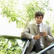Attractive businessman leaning on a car's top while using a smart phone — ストック写真