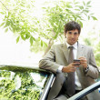Stock Photo: Attractive businessmleaning on car's top while using smart phone