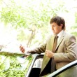 Stock Photo: Attractive young businessmusing smart phone while leaning on door of his car