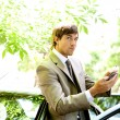 Stock Photo: Attractive young businessman using a digital tablet while leaning on the door of his car