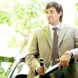 Stock Photo: Young businessmholding cell phone while leaning on his car door