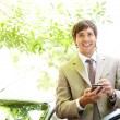 Attractive young businessman using a digital tablet while leaning on the door of his car — Stock Photo