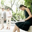 Two businessmen walking in the street and looking at a sexy businesswoman — Stock Photo