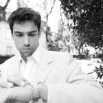 svartvita porträtt av en ung attraktiv affärsman tittar på tiden i sin klocka — Stockfoto