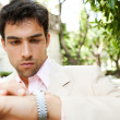 Young attractive businessman looking at the time in his watch - Stock Photo