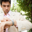 Young attractive businessman looking at the time in his watch - Foto Stock