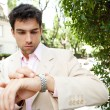 图库照片: Young attractive businessman looking at the time in his watch