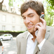 Attractive young businessmusing hands free ear piece device to make phone call — Stock Photo #21929413