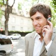 Young attractive businessman using an ear phone device to speak on his cell phone  — Stock Photo