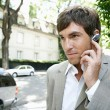 Stock Photo: Young businessmusing ear piece microphone to make phone call.