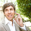 Attractive young businessman using a hands free ear piece device — Stock Photo