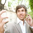 Stock Photo: Expressive young businessman using an ear piece device