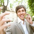 Espressive young businessman using an ear piece device — Stock Photo #21929713