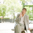 Stock Photo: Businessmsitting on bench in financial district