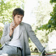Stock Photo: Attractive young businessmusing different technology