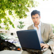 Attractive young businessman using a laptop computer — Stock Photo