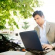 Attractive young businessman using a laptop computer while sitting on a bench — Stock Photo