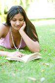 Parkta yeşil çim döşeme iken kitap okuyarak bir hintli kız portresi. — Stok fotoğraf