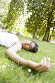 Indian girl laying down on green grass in a park on a sunny day. — Stock Photo