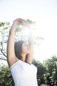 Jeune femme indienne qui s'étend et faire du yoga dans le parc avec le soleil filtrant à travers ses bras. — Photo