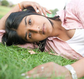 Teenage girl resting on green grass in the park. — Stock Photo