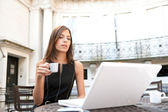 Young attractive businesswoman sitting in a luxurious coffee shop terrace with her laptop — Stock Photo